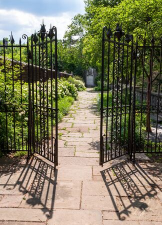 A stone walkway behind an opened wrought iron fence in a garden at Mellon Park, Pittsburgh, Pennsylvania, USA