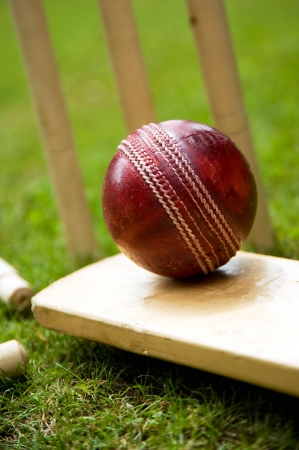 matches: Red leather cricket ball on grass with stumps Stock Photo