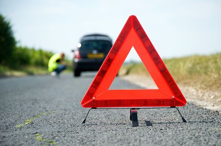 Red warning triangle with a broken down car Stock Photo
