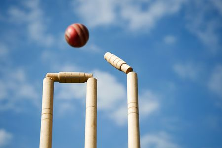 cricket game: Cricket stumps and bails hit by a ball