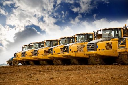 dump truck: Row of yellow heavy tipper trucks