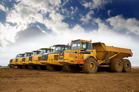 Row of yellow heavy tipper trucks photo