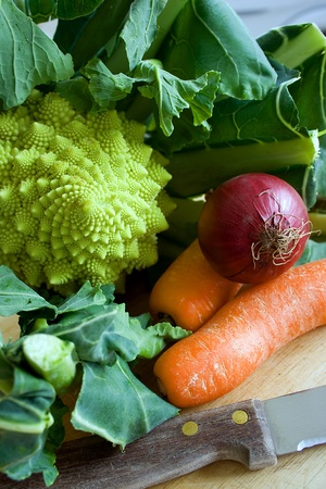 Romanesco broccoli, carrots and onion on a chopping board Stock Photo