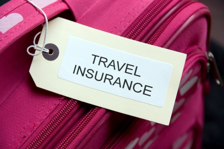 luggage tag: Travel Insurance label tied to a suitcase