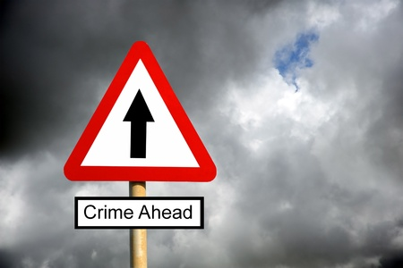Red triangle Crime Ahead warning sign against a cloudy stormy sky Stock Photo - 12747716