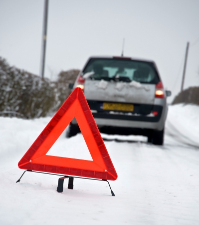 drive crash: Broken down vehicle in winter snow conditions with red warning triangle Stock Photo
