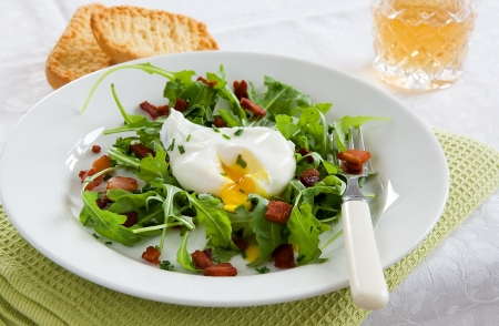 A green French bistro style salad on a white plate and table setting Stock Photo