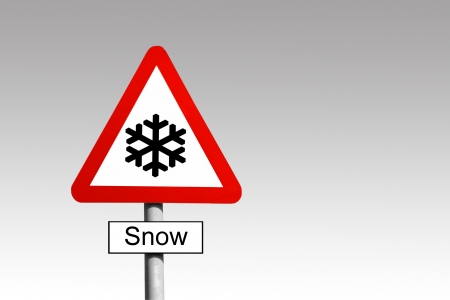 Snow Warning triangle road sign against a grey sky Stock Photo