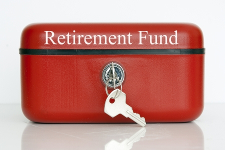 A closed red metal cash tin with Retirement Fund notice against a white background Stock Photo