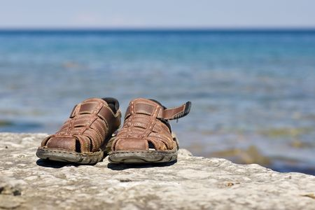 A pair of brown sandals on a rocky ledge, with an expance of blue water and sky behind. 版權商用圖片