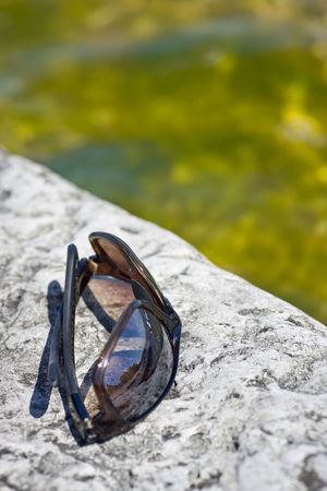 A closeup of a folded pair of sunglasses, on a porous rock, showing its detail. 版權商用圖片