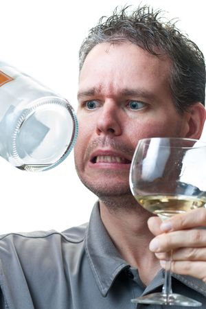 A man holding a wine glass and bottle, with exagerated concern on his face as he examines the empty bottle, isolated on white.