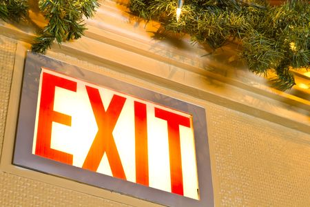A closeup of an exit sign, lit, with green garland and white christmas lights beside. 版權商用圖片