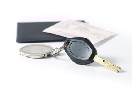 protector: Car keys attached to a keychain, with an insurance slip on top of a black protector in behind, isolated on white. Stock Photo