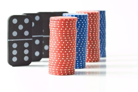 Stacks of red and blue poker chips with black dominoes behind, isolated on white. Stock Photo