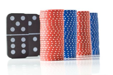Stacks of red and blue poker chips with black dominoes behind, isolated on white. 版權商用圖片