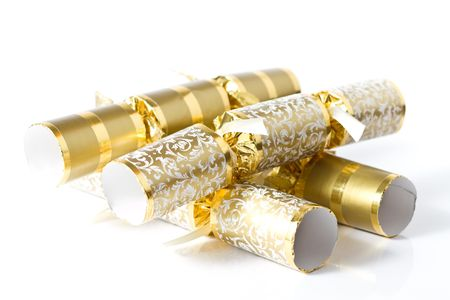 A bunch of gold Christmas crackers with a slight reflection,isolated on white.