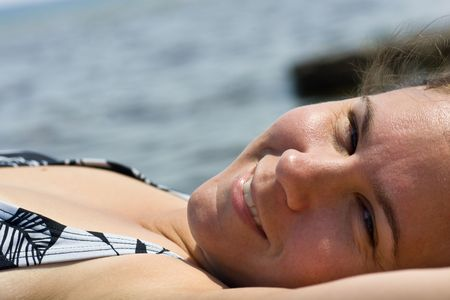 A closeup of a womans face lying out in the sun, smiling at the camera. Stock Photo