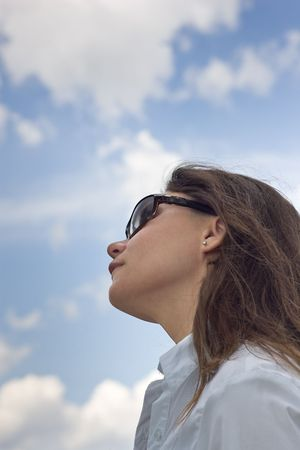Looking up at a womans face, as she looks up to the sky, with a blue sky dotted with clouds i the background.