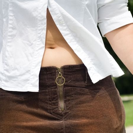 Closeup of a woman's mid-section, revealed by an unbuttoned white shirt, showing the belly button. 版權商用圖片