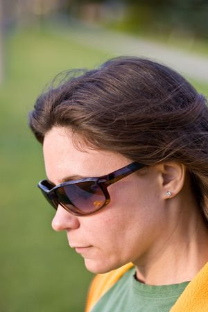 A woman with long hair and sunglasses looking down ,with a blurred background. 版權商用圖片