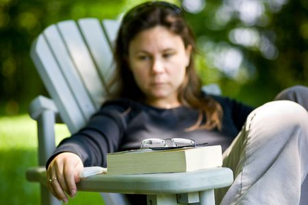 A woman contemplating, after reading a book, sitting in front of her, on the arm of an adirondack chair.