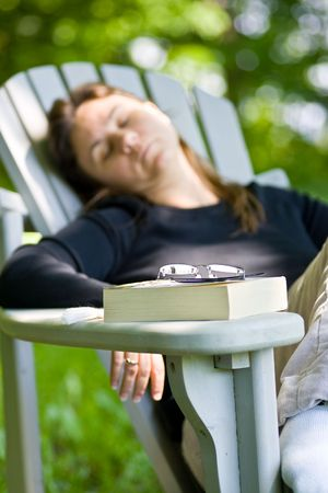 A woman outside,  in an adirondack chair, dosing off, with a closed paperback book on the arm of her chair.