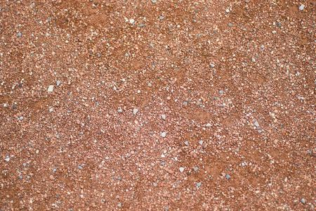 The texture of the infield of a baseball diamond, made up of crushed stone and a redish brown clay.