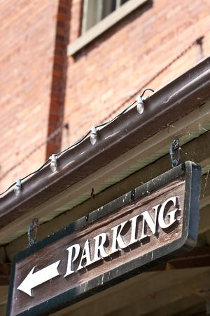 A closeup of a custom parking sign with a directional arrow, hanging from the roof of a building.
