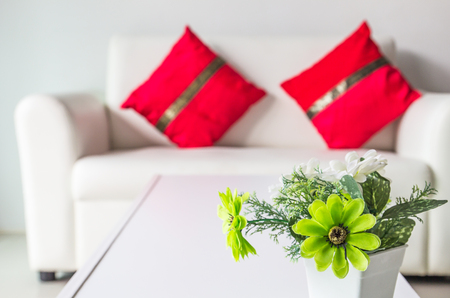 plastic flowers on white table and white sofa with cushions in living room