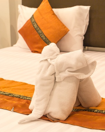 white elephant towels and orange cushions on bed in hotel room