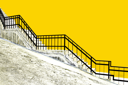 tiled stairs and black steel railing with yellow concrete wall on ramp road Imagens