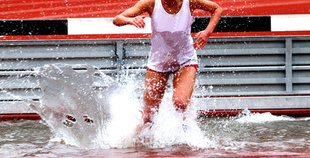 A high school girl running in the steeplechase race landing in the water