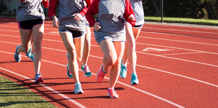 A group of girls train together on a red track running clockwise
