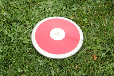 A red girls 1K discus rests on the green grass