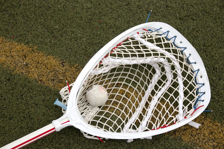 A red and white lacrosse goalie stick on a green turf field with a ball in the net Stock fotó - 76076318
