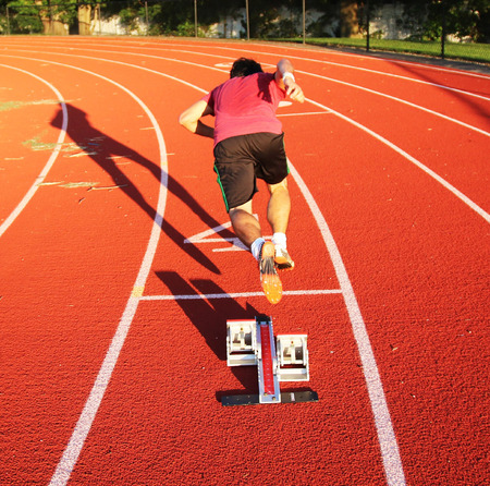 A runner sprints our of starting blocks on a red track