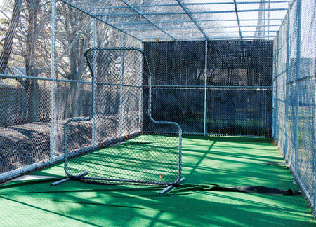 backstop: The view from inside a baseball batting cage from behind the pitching screen