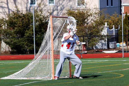 Lacrosse goalie stands in front of the net ready to make a save during a game