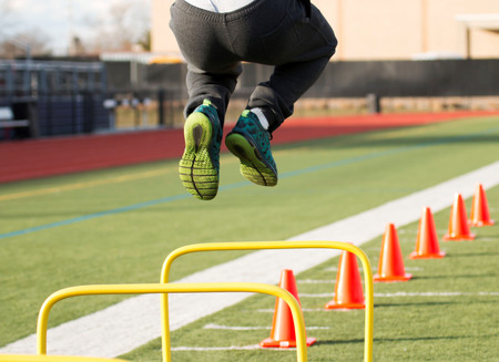A track and field athlete jumps over yellow hurdles before he runs over orange cones, all on a green turf field
