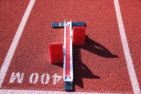 Rode startblokken op een rode baan op de startlijn van 400 meter
