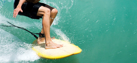 The bottom half of a male surfer riding a wave in clear water