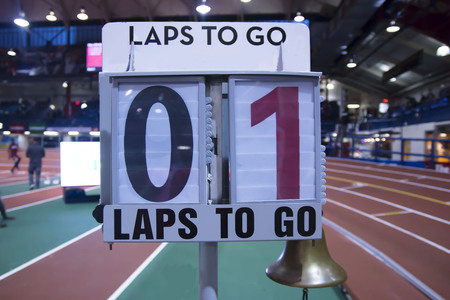 A lap counter is set up next to the finish line to let the runners know how many laps to go in an indoor track and field arena 版權商用圖片