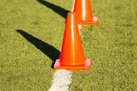 Orange cones on a white line on a green turf field Stock fotó - 76134147