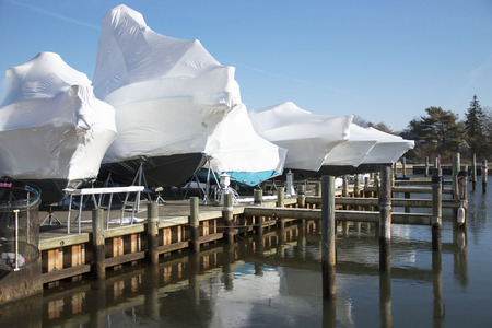 Boats shrink wrapped and stored on the docks for winter Stock Photo