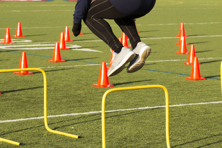 An athlete works out jumping over yellow hurdles on a green turf field with orange cones on it Stock fotó