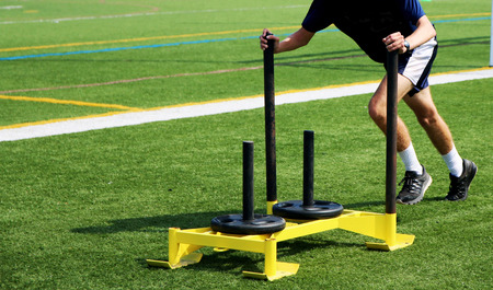 Athlete pushing a weighted sled for speed training