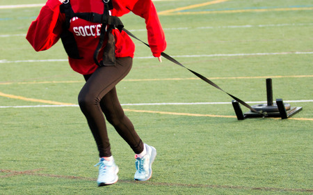 A girl running while pulling a weighted sled on a green turf field,