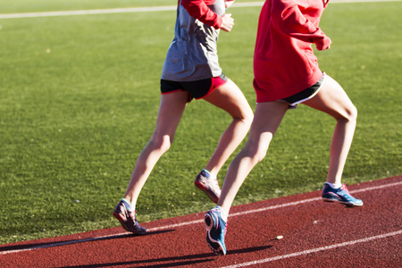 be or not to be: Two girls training for speed together on a red track