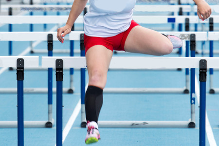 bounding: High school girl racing the hurdles at a track and field competition